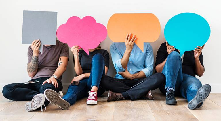 Four people hold up various cardboard quote bubbles in front of their faces while sitting on the floor.