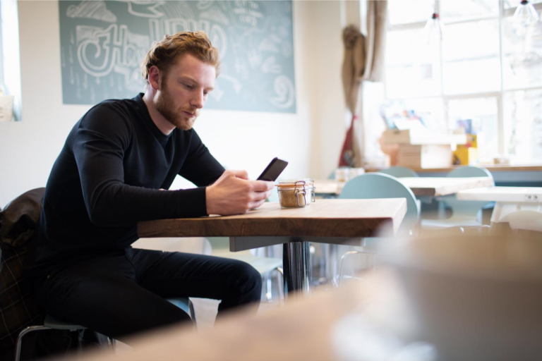 A man sits in a coffee shop and shops online using his mobile phone.